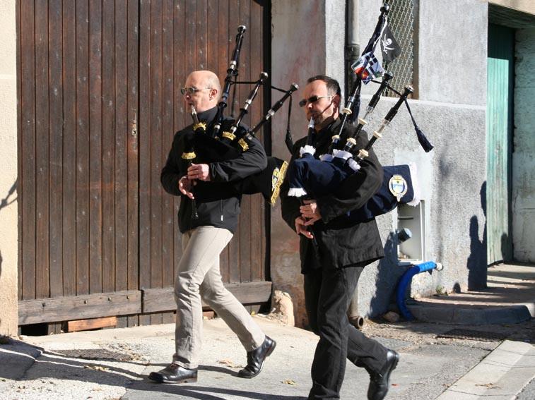 Derrière les portes drapeaux , Gérard et Olivier entrainent le défilé vers le monument aux morts du cimetière de Carnoules